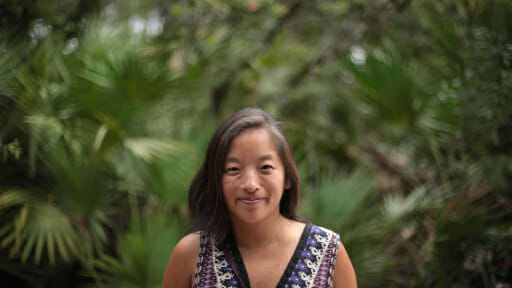 OneBeat co-director Elena Moon Park standing in front of a lush forest of tropical plants.